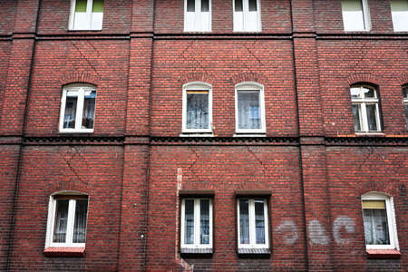 Windows in the brick facade of a historic house in Poznan