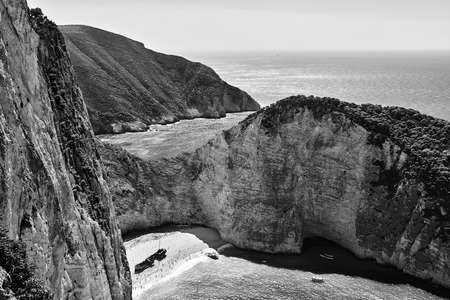 Rocky cliffs, shipwreck and people on the beach Navagio on Zakynthos island in Greece, monochrome
