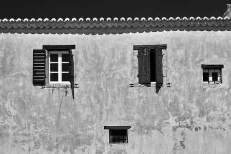 Windows in the wall of the historic Orthodox monastery in Zakynthos, Greece, monochrome