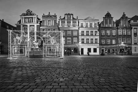 The Market Square with historic tenement houses and christmas decorations in city of Poznan, monochrome