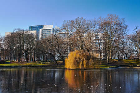Frozen pond in the city park and modern buildings from Poznan