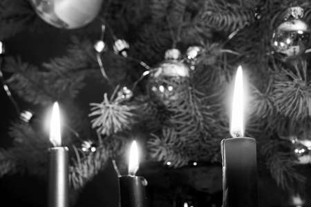 A candle flame on a background of decorated spruce branches of a Christmas tree in Poland, monochrome