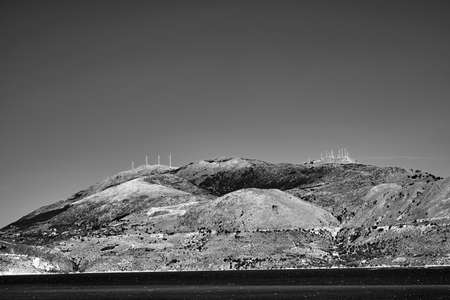 rocky coast and windmills on a hill on the island of Kefalonia in Greece, monochrome Stock Photo