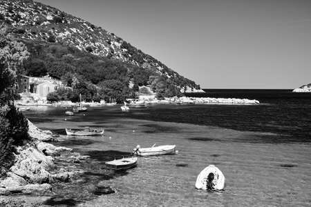 Boats in a rocky bay on the island of Kefalonia in Greece, monochrome Stock Photo