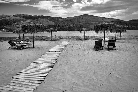 Umbrellas on an empty sandy beach on Kefalonia island in Greece, monochrome