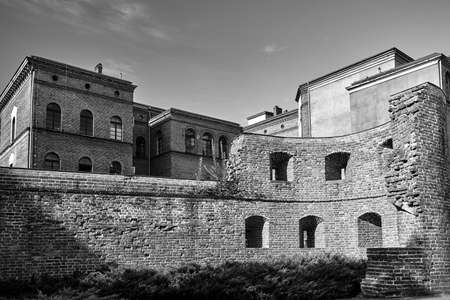 ruin of a medieval tower and historic tenement houses in the city of Poznan, monochrome