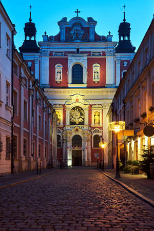 The facade of a baroque church decorated with columns and statues in the evening in Poznan