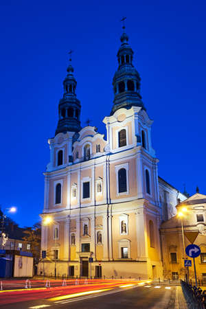 facade and bell towers of a baroque church during the night in Poznan