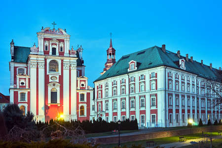 The facade of the Baroque Catholic Church and a historic religious building in the evening in Poznan Stock Photo