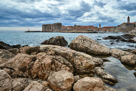 Coastal rocks and medieval defensive walls in the city of Dubrovnik in Croatia Stock Photo