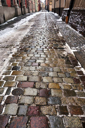 Melting snow on the road with granite paving stones in Poznan Stock Photo