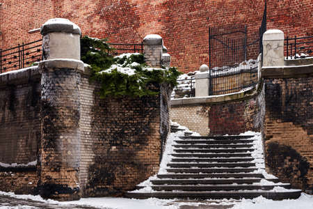 snow on the stairs and medieval stone and brick wall in Poznan