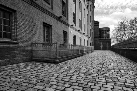 paved street and renovated buildings of an old brewery in the city of Poznan, monochrome Stock Photo