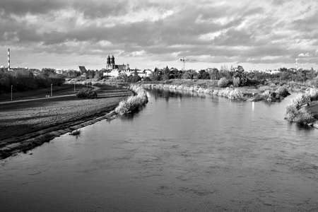 Urban landscape with river Warta and the cathedral towers in the fall in Poznan, monochrome