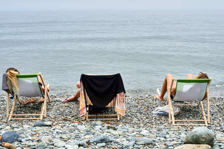 Girls on deck chairs on a pebble beach by the Aegean Sea in Greece Stock Photo