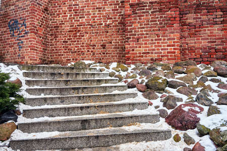 snow on stone steps and a medieval brick wall in Poznan
