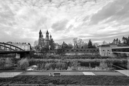 a modern footbridge, historic walls and gothic bell towers of the cathedral in Poznan, monochrome