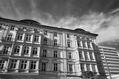 the facade of a historic tenement house and a modern office building in Poznan, monochrome