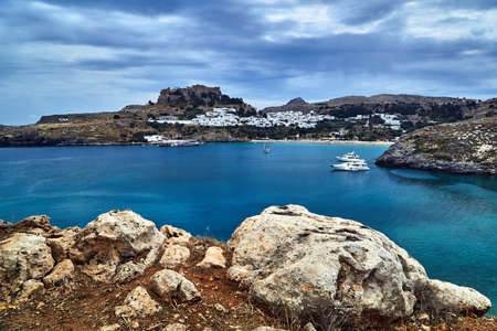 a bay with a rocky coast, the town of Lindos and a medieval fortress on the island of Rhodes