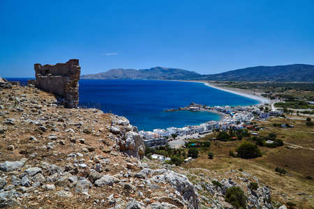 Ruins of a medieval fortress and the sea coast with the port and town on the island of Rhodes, Greece Editorial