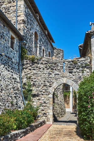 A medieval gate in a stone, historic buildings in the city of Saint-Vincent in France
