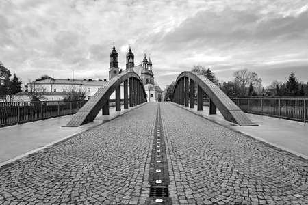 The steel structure of the bridge and the towers of the Gothic Catholic cathedral in Poznan, monochrome