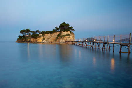 islet: Small islet Agios Sostis connected with a bridge to Zakynthos island, Greece at sunse