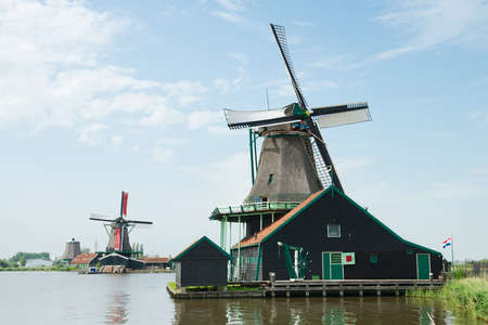 traditional windmill: Traditional windmill near the river at Zaanse Schans, Holland Stock Photo