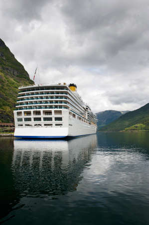 Big luxury cruise liner in the port of Flam reflecting in still clear waters of the fjord, Norway