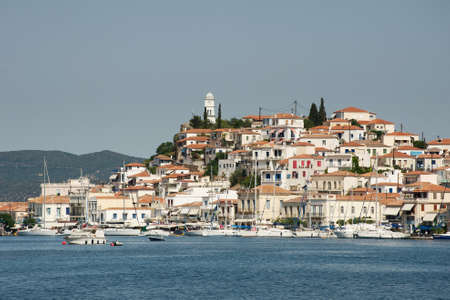 poros: View of the village and a tower on the hill, Poros island, Greece