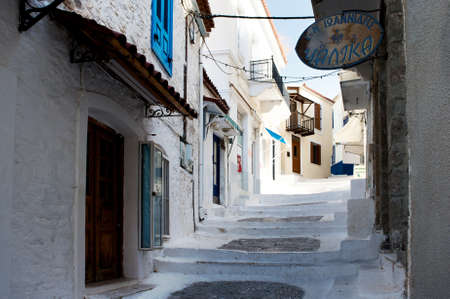 Street with white road and old houses in the village at the Poros island, Greece photo