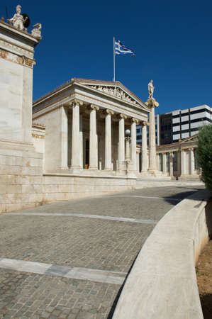 View of the National Library building with roadway, statues and a flag, Athens, Greece