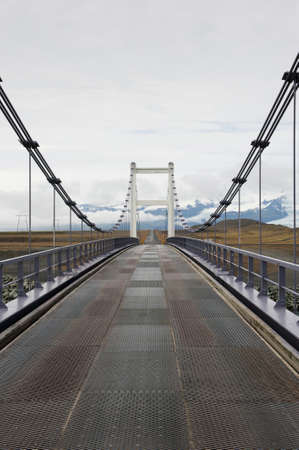 Metallic bridge and straight asphalt road leading to the mountains in a distance, near Jokulsarlon, Iceland photo