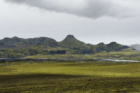 crater highlands: Moss field with volcanic crater in a distance on a cloudy day, lakagigar, Iceland