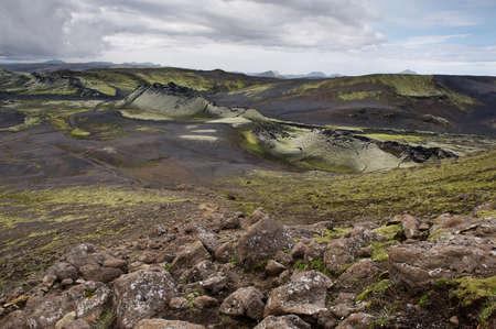 crater highlands: Vista del parque nacional Lakag�gar con rocas en primer plano en un d�a nublado, Islandia Foto de archivo