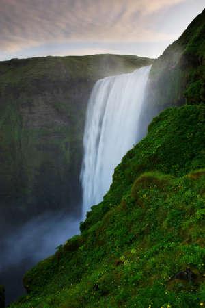 skogafoss waterfall: Clouds above Skogafoss waterfall and cliffs around it, South Iceland