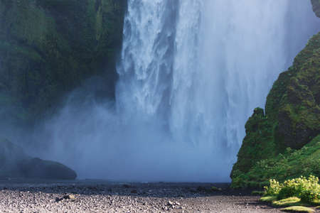 Bottom part of falling waters of Skogafoss waterfall on a sunny summer day, South Iceland photo