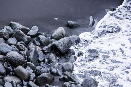 Rocks on the black sand and sea waves captured from above near Vík í Mýrdal, South Iceland photo