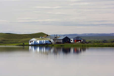 Small farm reflecting in still water on a cloudy summer day, Myvatn lake, Iceland