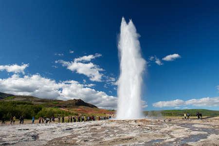 iceland: Impressive eruption of the biggest active geysir, Strokkur, with tourists waiting around, Golden circle, Iceland Stock Photo