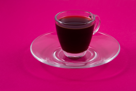 A cup of coffee bp made of clear glass on a bright background of fuchsia.