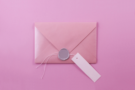 Pink envelope-letter with a wax seal and a paper tag for a signature on a light purple background.