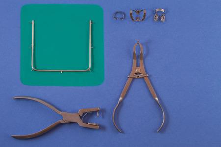 Werkzeuge für die Installation des Kofferdamms. Kofferdam und Klemme liegen auf dem Tisch einen blauen Hintergrund.