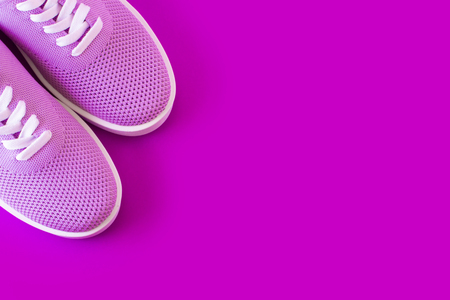 Light purple sneakers layout on a bright violet background with a place for an inscription. Stock Photo