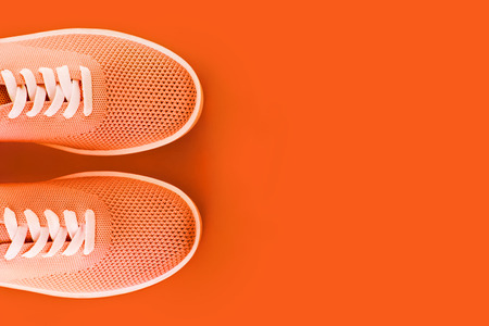 Bright orange sneakers on an orange background with a place for an inscription.