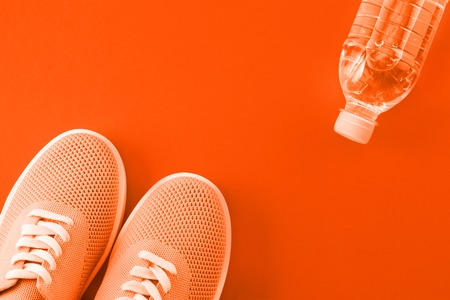 Light orange sneakers and a bottle of water on a orange background with a place for an inscription.