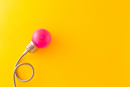 One pink decorative lamp on a bright yellow background and symbolize insight and various creative ideas.