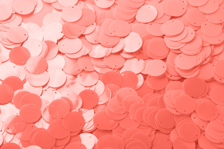 Trend photography on the theme of the color of the year 2019 - Living Coral. Large shiny semi-matt pink sequins fully filling the background space.