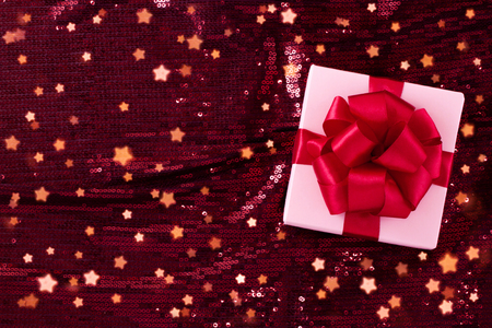 Light pastel pink box tied with a red satin ribbon with a bow of pop-pop on a dark burgundy shiny sequins background with a magical holiday stars.