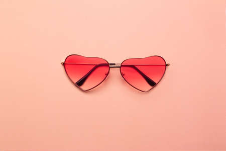 Trend photo on the theme of fashionable orange hue this season. Bright coral heart-shaped glasses on a orange paper background. 免版税图像